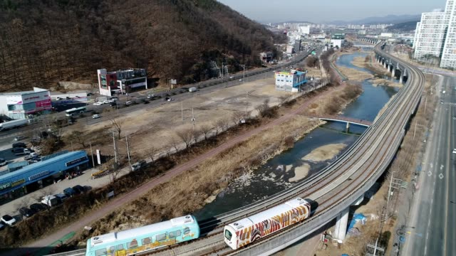 aerial view of running light-rail transit and cityscape in cheoingu, yongin city at daytime - zebramuster stock-videos und b-roll-filmmaterial