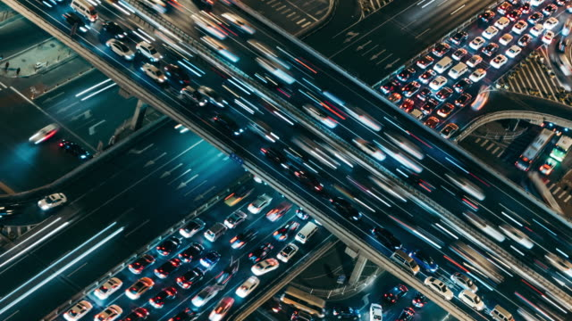 t/l cu ha pan aerial view of rush hour traffic on multiple highways at night / beijing, china - pechino video stock e b–roll