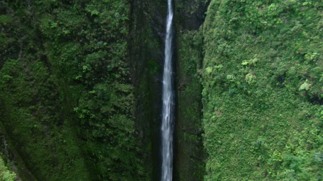 Aerial view of Sacred Falls, tilting down to reveal the pool at the bottom of a deep well.