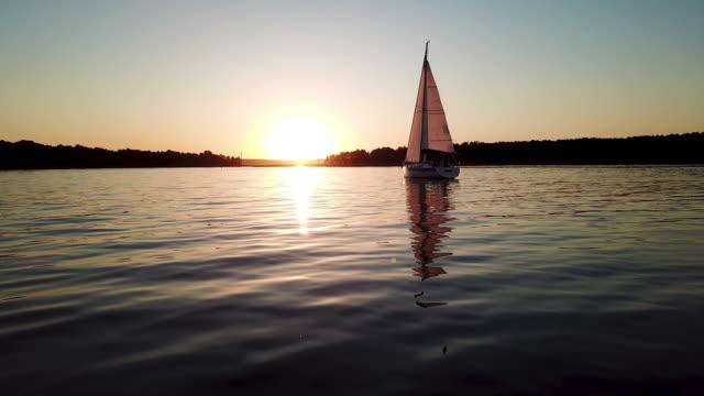ゆっくりと湖に浮かぶ帆船の空中風景。日没 - ヨット点の映像素材/bロール