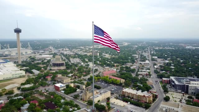 aerial view of san antonio, texas with american flag - san antonio texas stock videos and b-roll footage