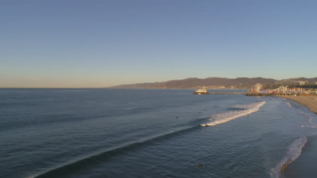 Aerial view of Santa Monica surfers drone pov at sunrise