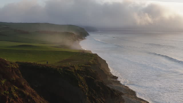 aerial view of sea cliffs and crashing surf, at sunrise - power in nature stock videos & royalty-free footage