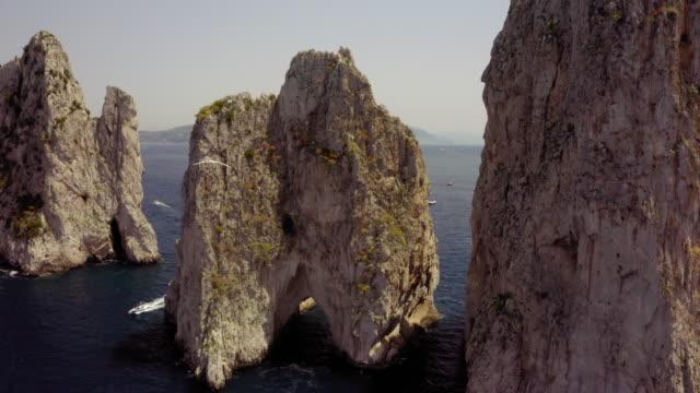 vídeos de stock, filmes e b-roll de aerial view of seagull flying over sea near stack rocks on sunny day, sea bird moving over water against rocky mountain - capri, italy - coluna de calcário marítimo