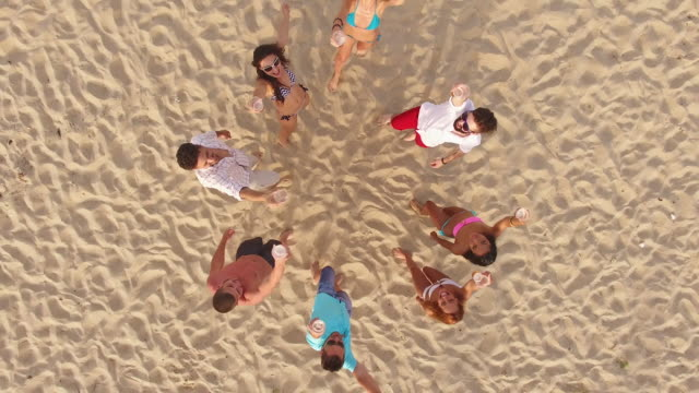 4k aerial view of seaside and friends drinking beer on beach - celebratory toast stock videos & royalty-free footage