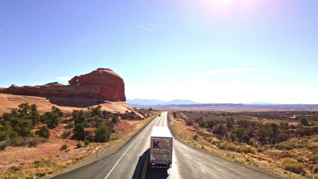 aerial view of semi-truck on a desert highway - arches national park stock videos & royalty-free footage