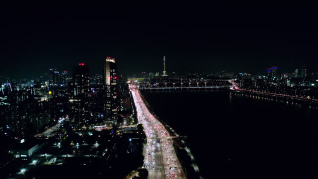 aerial view of seoul downtown city skyline with light trails on expressway and bridge cross over han river at night in seoul city, south korea. - seoul stock videos & royalty-free footage