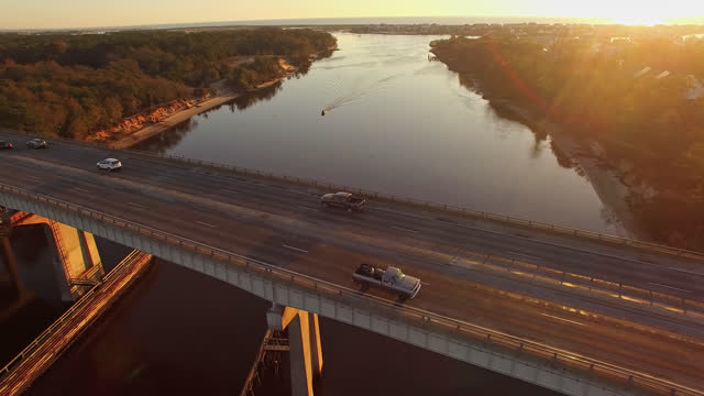 drone. aerial view of serene sunrise passing over snows cut bridge and canal near carolina beach - wilmington north carolina stock-videos und b-roll-filmmaterial