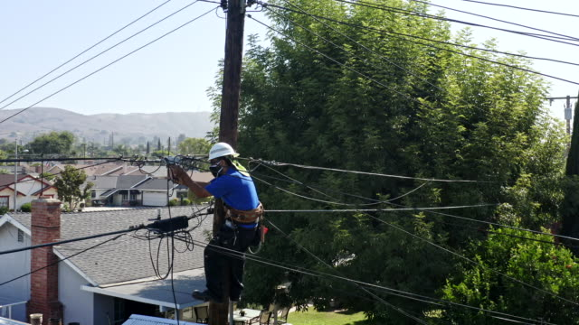 aerial view of service technician working on lines - pole stock videos & royalty-free footage