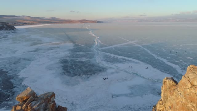 vídeos de stock e filmes b-roll de aerial view of shaman ka rock landmark in the frozen baikal lake in the morning, russia - congelado