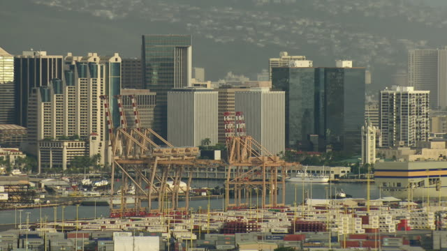 aerial view of shipping containers and cranes on sand island with honolulu skyscrapers in distance. - oahu stock videos and b-roll footage