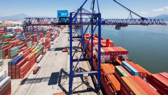 vídeos de stock, filmes e b-roll de tl, ws, ha aerial view of shipping containers being unloaded from a cargo ship in a busy port / paranagua, brazil - transporte assunto