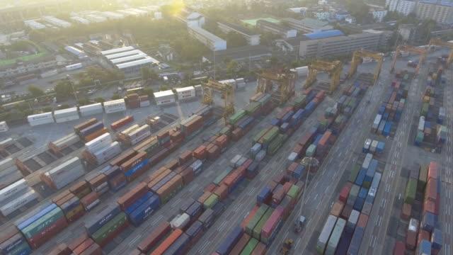 vidéos et rushes de vue aérienne des conteneurs d'expédition étant déchargé d'un navire de fret dans un port occupé - décharger