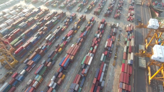 Aerial view of shipping containers being unloaded from a cargo ship in a busy port