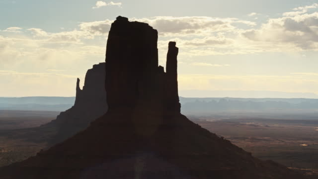 aerial view of silhouetted mitten buttes in monument valley - mitten stock videos & royalty-free footage