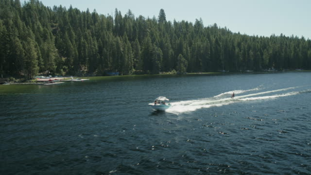 aerial view of ski boat pulling an air chair rider - barca a motore video stock e b–roll