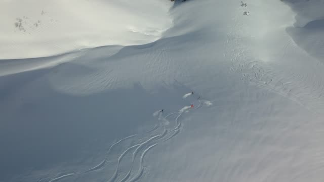 stockvideo's en b-roll-footage met luchtfoto van skiërs aflopende besneeuwde berg - vier personen