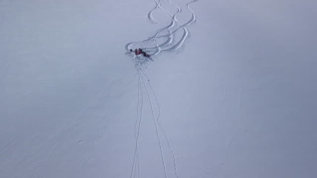 aerial view of skiers performing avalanche test on snowy mountain - avalanche stock videos and b-roll footage