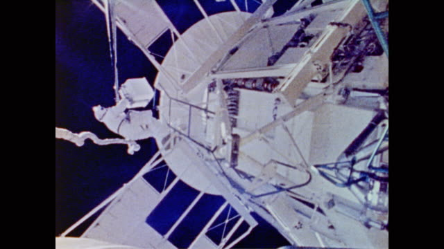 stockvideo's en b-roll-footage met aerial view of skylab floating in space as well as interior shots of the astronauts, moon walk and space station repairs before a scientist plucks a... - 1973