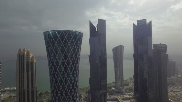 vídeos de stock e filmes b-roll de aerial view of skyscrapers by sea against cloudy sky, doha, qatar - catar