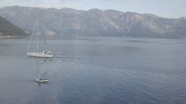 aerial view of small boat floating in kotor bay in adriatic sea - yacht stock videos & royalty-free footage