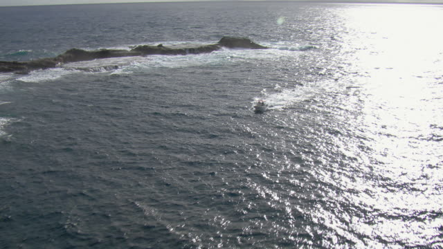 Aerial view of small boat near Mokuhooniki rock off the coast of Molokai, Hawaii.
