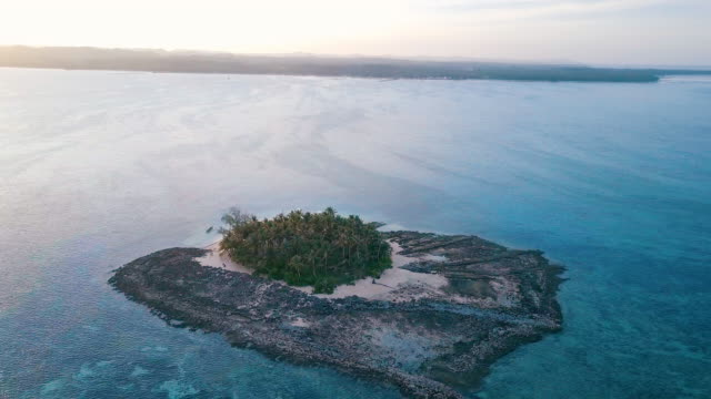 aerial (drone) view of small tropical island at sunset - piccolo video stock e b–roll