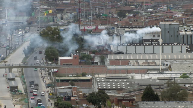 aerial view of smoke emitting from factory smoke stack in bogota, colombia - luftverschmutzung stock-videos und b-roll-filmmaterial