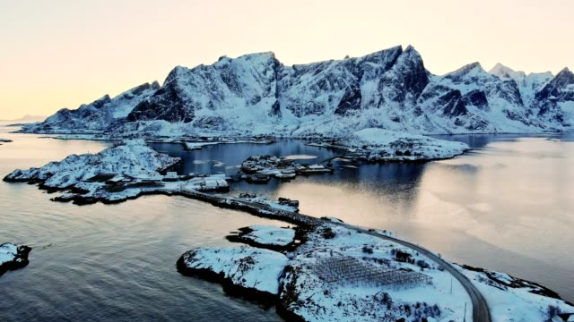aerial view of snow mountain with fishing village in arctic ocean at sunset - arctic stock videos & royalty-free footage