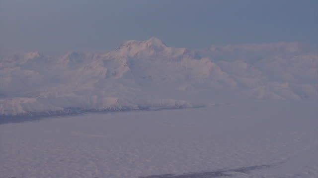 Aerial view of snow-capped mountains at sunrise