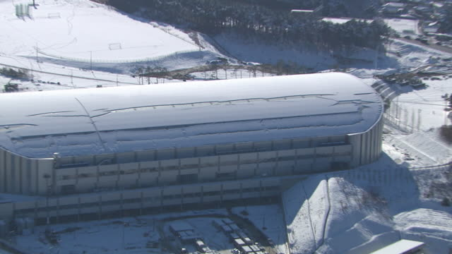 Aerial view of snow-covered Hockey Field and Ice Arena in distance (Stadium for 2018 Winter Olympics)