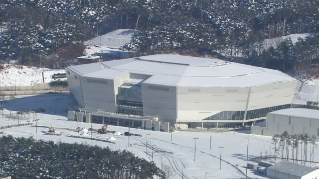 aerial view of snow-covered hockey field (stadium for 2018 winter olympics) - field hockey stock videos and b-roll footage