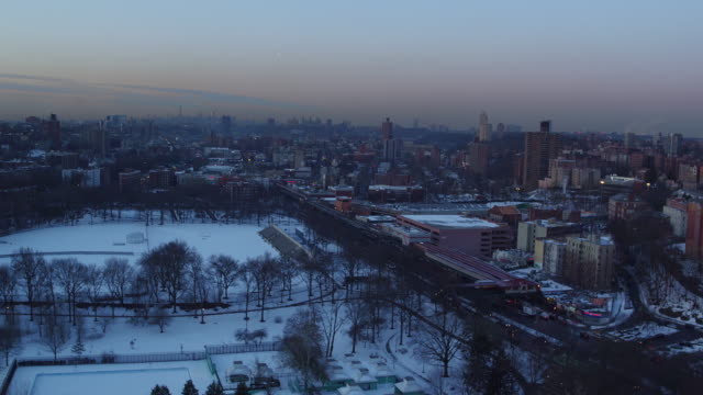 aerial view of snow-covered sports fields in urban neighborhood, with manhattan in distance - football pitch stock videos and b-roll footage