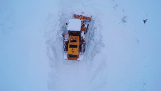 vídeos y material grabado en eventos de stock de aerial view of snowplows clearing snow covered road in early evening. - quitanieves