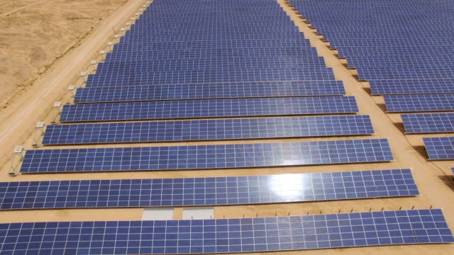 aerial view of  solar array in the desert with sun reflecting on the panels - solar panels stock videos & royalty-free footage