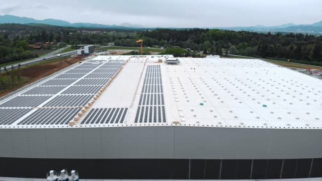 aerial view of solar panels being installed on the roof of a factory - self storage stock videos and b-roll footage