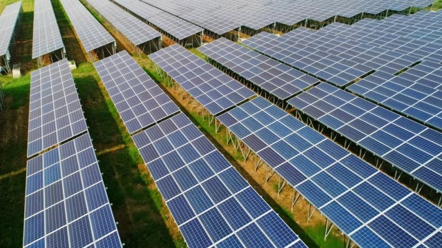 vídeos de stock e filmes b-roll de 4k aerial view of solar panels farm (solar cell) with sunlight - green