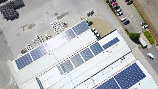 aerial view of solar panels on the roof of a large self sufficient storage facility - warehouse stock videos & royalty-free footage