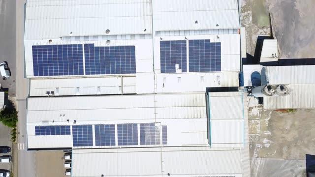 vídeos y material grabado en eventos de stock de vista aérea de los paneles solares en el techo de una gran instalación de almacenamiento autosuficiente - top