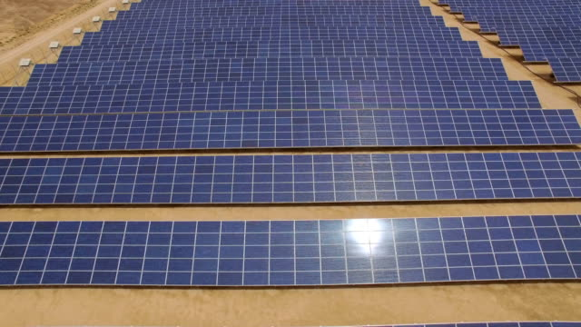 aerial view of  solar power plant in the desert with sun reflecting on the panels - solar panels stock videos & royalty-free footage