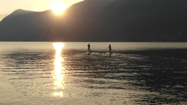 stockvideo's en b-roll-footage met aerial view of stand up paddle boarders on calm lake at sunrise - peddelen