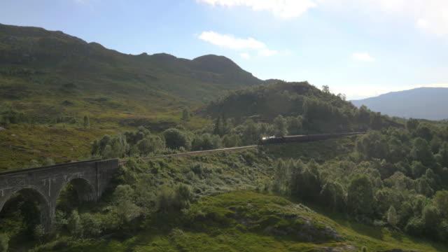aerial view of steam train crossing glenfinnan viaduct - zug mit dampflokomotive stock-videos und b-roll-filmmaterial
