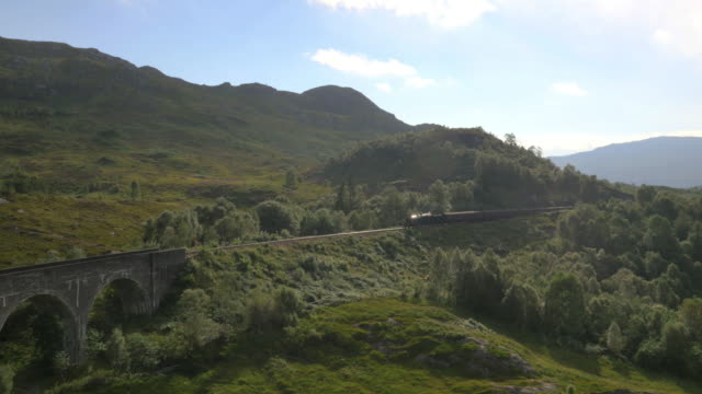 aerial view of steam train crossing glenfinnan viaduct - viaduct stock videos & royalty-free footage
