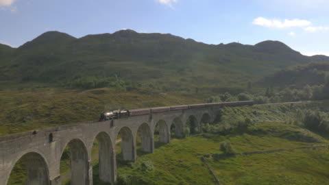 vidéos et rushes de aerial view of steam train crossing glenfinnan viaduct - lieu touristique