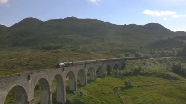 stockvideo's en b-roll-footage met aerial view of steam train crossing glenfinnan viaduct - famous place