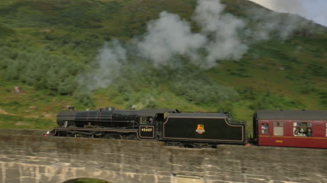 stockvideo's en b-roll-footage met aerial view of steam train crossing glenfinnan viaduct - waterdamp