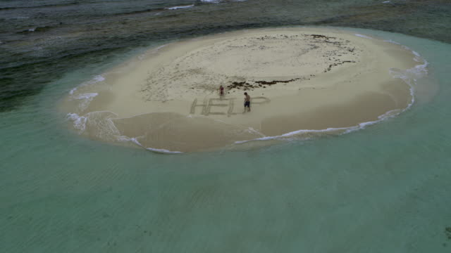 aerial view of stranded couple drawing help in sand on remote island beach / grenada - perso video stock e b–roll