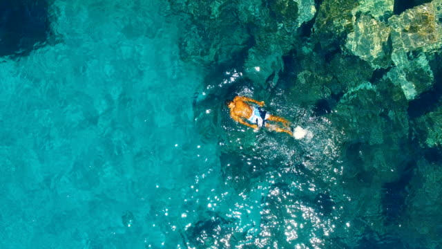 aerial view of strong man floating in the water in amazing, unspoiled and idyllic beach - 水に浮かぶ点の映像素材/bロール
