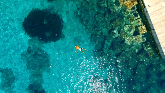 aerial view of strong man floating in the water in amazing, unspoiled and idyllic beach - floating on water stock videos & royalty-free footage