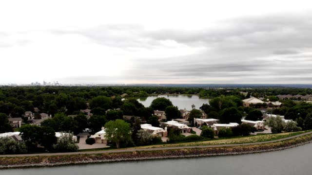 Aerial view of suburban homes and urban reservoirs on a cloudy day in Lakewood Colorado
